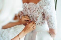 les demoiselles d'honneur aident à porter une robe de dentelle de mariage Image libre de droits