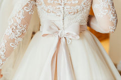 les demoiselles d'honneur aident à porter une robe de dentelle de mariage Photos stock