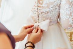 les demoiselles d'honneur aident à porter une robe de dentelle de mariage Photographie stock