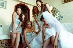 Les demoiselles d'honneur aident la jeune mariée à mettre dessus des chaussures tandis qu'elle s'assied sur le sof Photographie stock