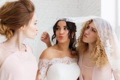 Les demoiselles d'honneur embrassent la belle jeune mariée se tenant dans l'intérieur de chambre de grenier Portrait en gros plan Images stock