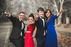 Les demoiselles d'honneur et les garçons d'honneur du mariage couplent la pose en parc Photo libre de droits