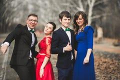 Les demoiselles d'honneur et les garçons d'honneur du mariage couplent la pose en parc Image libre de droits