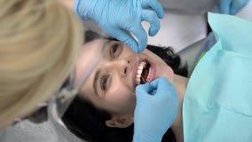Les dents de la jolie femme nettoyant dans la clinique dentaire banque de vidéos