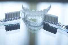 Les dents dentaires invisibles encadre des arrêtoirs et le toothbrus de dispositifs d'alignement photos stock