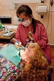 Les dents du patient de nettoyage d'hygiéniste dentaire images stock