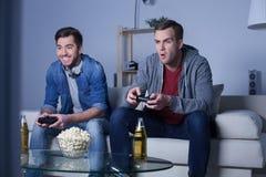 Les deux amis gais jouent le jeu vidéo Image libre de droits