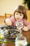 les Deux-années de fille mange des moules Photographie stock