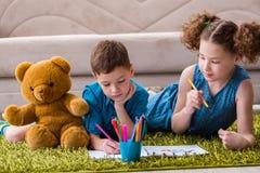 Les deux enfants dessinant des photos se trouvant sur la porte photo libre de droits