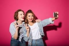 Les deux femmes gaies font le selfie par le téléphone Photo stock