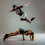 Les deux hanche de danse de jeune fille et de garçon sautent à cloche-pied dans le studio photographie stock libre de droits