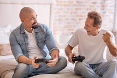 Les deux hommes avec plaisir jouant avec le jeu consolent à la maison Photos libres de droits