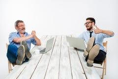 Les deux hommes d'affaires avec des jambes au-dessus de la table travaillant sur des ordinateurs portables Photographie stock libre de droits