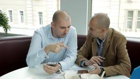 Les deux jeunes au déjeuner en café potable de café et nouilles de consommation discutant des affaires Travail, nourriture, télép banque de vidéos