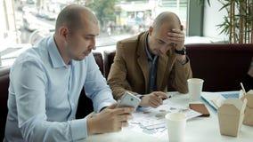 Les deux jeunes au déjeuner en café potable de café et nouilles de consommation discutant des affaires Travail, nourriture, télép clips vidéos