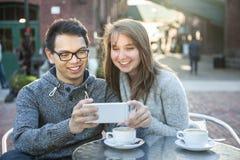 Les deux jeunes avec le smartphone en café Photos libres de droits