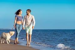 Les deux jeunes courant sur la plage embrassant et se tenant fortement avec le chien Photographie stock