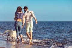 Les deux jeunes courant sur la plage embrassant et se tenant fortement avec le chien Photos libres de droits