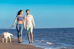 Les deux jeunes courant sur la plage embrassant et se tenant fortement avec le chien Photographie stock libre de droits