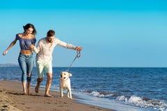 Les deux jeunes courant sur la plage embrassant et se tenant fortement avec le chien Images stock