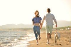 Les deux jeunes courant sur la plage embrassant et se tenant fortement avec le chien Photo stock