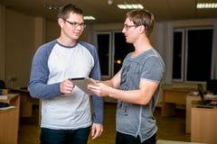 Les deux jeunes discutent un projet dans le bureau Se tenant l'un à côté de l'autre, l'un d'entre eux indique l'autre au sujet de image libre de droits