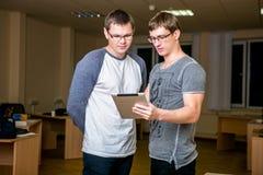 Les deux jeunes discutent un projet dans le bureau Se tenant l'un à côté de l'autre, l'un d'entre eux indique l'autre au sujet de photographie stock