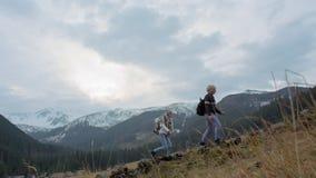 Les deux jeunes escaladent la montagne et l'homme aide Madame à s'élever clips vidéos