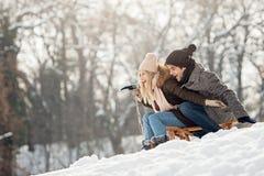 Les deux jeunes glissant sur un traîneau photo stock