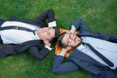 Les deux jeunes hommes d'affaires heureux dans un costume se trouvant dessus Photos stock