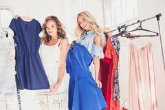 Les deux jeunes jolies filles regardant des robes et l'essayent tout en choisissant à la boutique Photos libres de droits