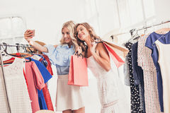 Les deux jeunes jolies filles regardant des robes et l'essayent tout en choisissant à la boutique Photos stock