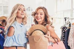 Les deux jeunes jolies filles regardant des robes et l'essayent tout en choisissant à la boutique Photographie stock libre de droits