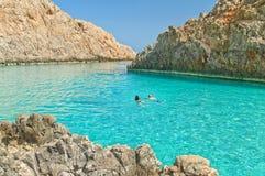 Les deux jeunes nageant en mer bleue le jour ensoleillé Images stock