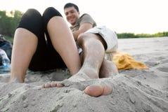Les deux jeunes s'asseyant sur la plage Photos stock