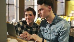 Les deux jeunes sourient, écoutant la musique dans leurs écouteurs et se dirigeant à quelque chose sur l'écran d'ordinateur porta clips vidéos