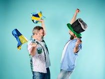 Les deux passionés du football avec un drapeau de l'Ukraine au-dessus du bleu Photographie stock libre de droits