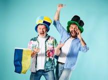 Les deux passionés du football avec un drapeau de l'Ukraine au-dessus du bleu Photographie stock