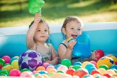 Les deux petits bébés jouant avec des jouets dans la piscine gonflable pendant le jour ensoleillé d'été Photo stock