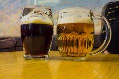 Les deux verres de bière tchèque sur une table en bois de baril Image libre de droits