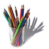 Les différentes couleurs crayonnent pour dessiner dans un verre sur un fond blanc photos libres de droits