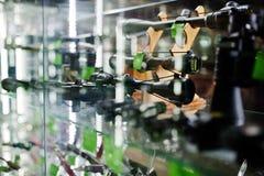 Les différents appareils optiques de visée sur des étagères stockent des armes sur le centre de boutique Photos stock