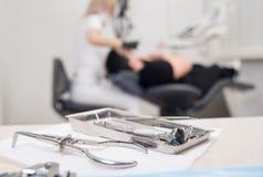 Les différents instruments dentaires professionnels, sur le dentiste brouillé de fond soigne le patient dans la clinique dentaire image libre de droits