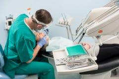 Les différents instruments dentaires professionnels, sur le dentiste brouillé de fond soigne le patient dans la clinique dentaire photos stock