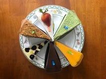 Les différents morceaux de gâteau découpés en tranches avec la bougie ont arrangé en circulaire Photographie stock libre de droits