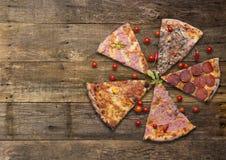 Les différents types de pizza ont coupé sur la table en bois Images stock