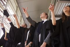 Les diplômés dans des robes jetant leur mortier embarque dans le ciel image stock