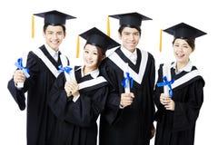 Les diplômés d'université dans l'obtention du diplôme habille la position et le sourire Photographie stock libre de droits