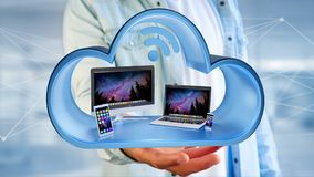 Les dispositifs aiment le smartphone, le comprimé ou l'ordinateur montrés dans un nuage Images stock
