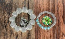 Les divers bracelets à la mode et élégants brochent et sonnent d'isolement sur le fond en bois foncé de vintage Images stock